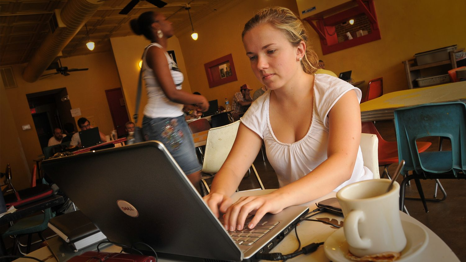 Woman completing coursework online from a coffee shop