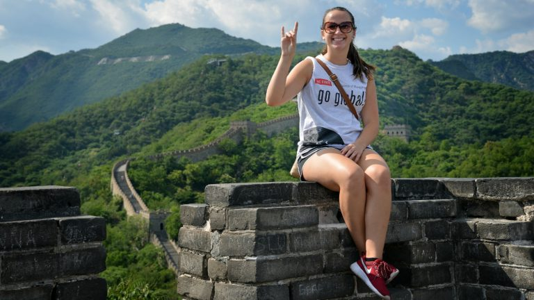 Study abroad student on top of Great Wall in China.
