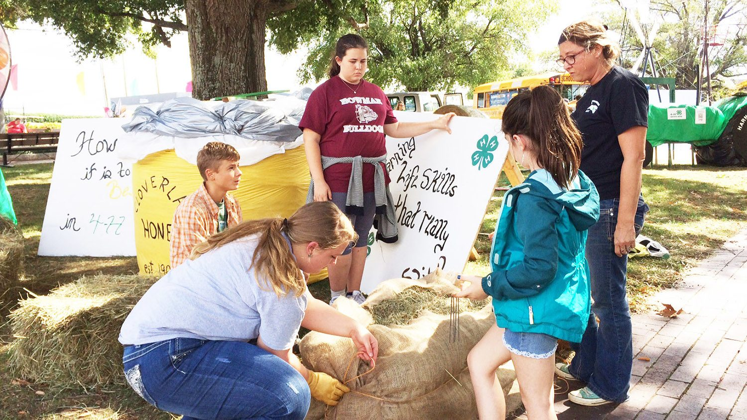 With the help of their 4-H agent and volunteer, Mitchell County 4-H'ers decorate hay bales at the State Fair.