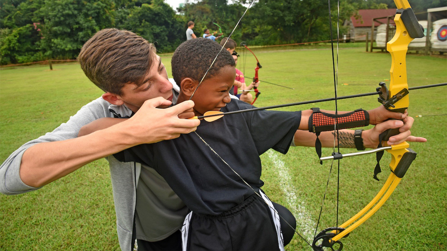 Young Caucasian male helping young African American boy with archery