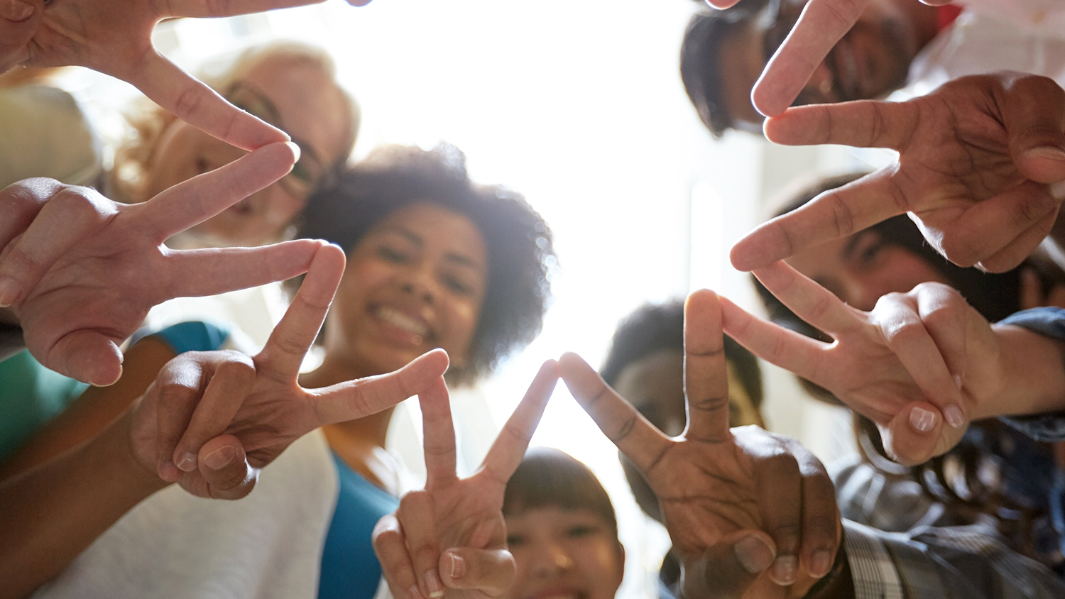 Friends holding peace sign around a circle.
