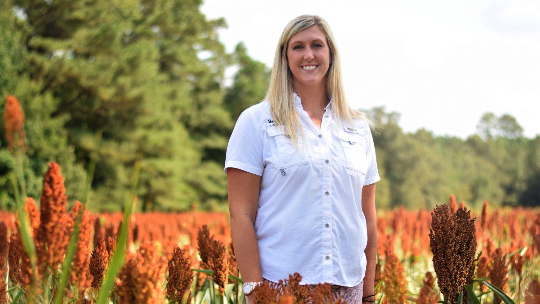 ABM alumna Rachel Grantham standing in a field.