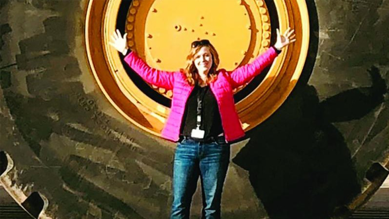 woman in front of large tire