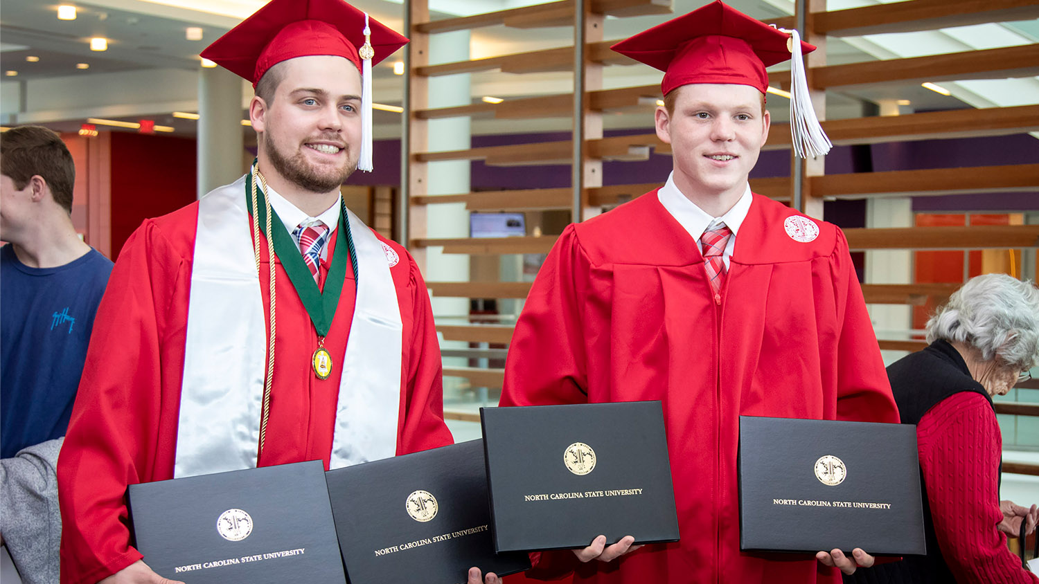 two AGI students standing with their diplomas.