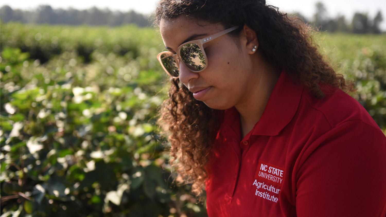 Student in sunglasses in a field.