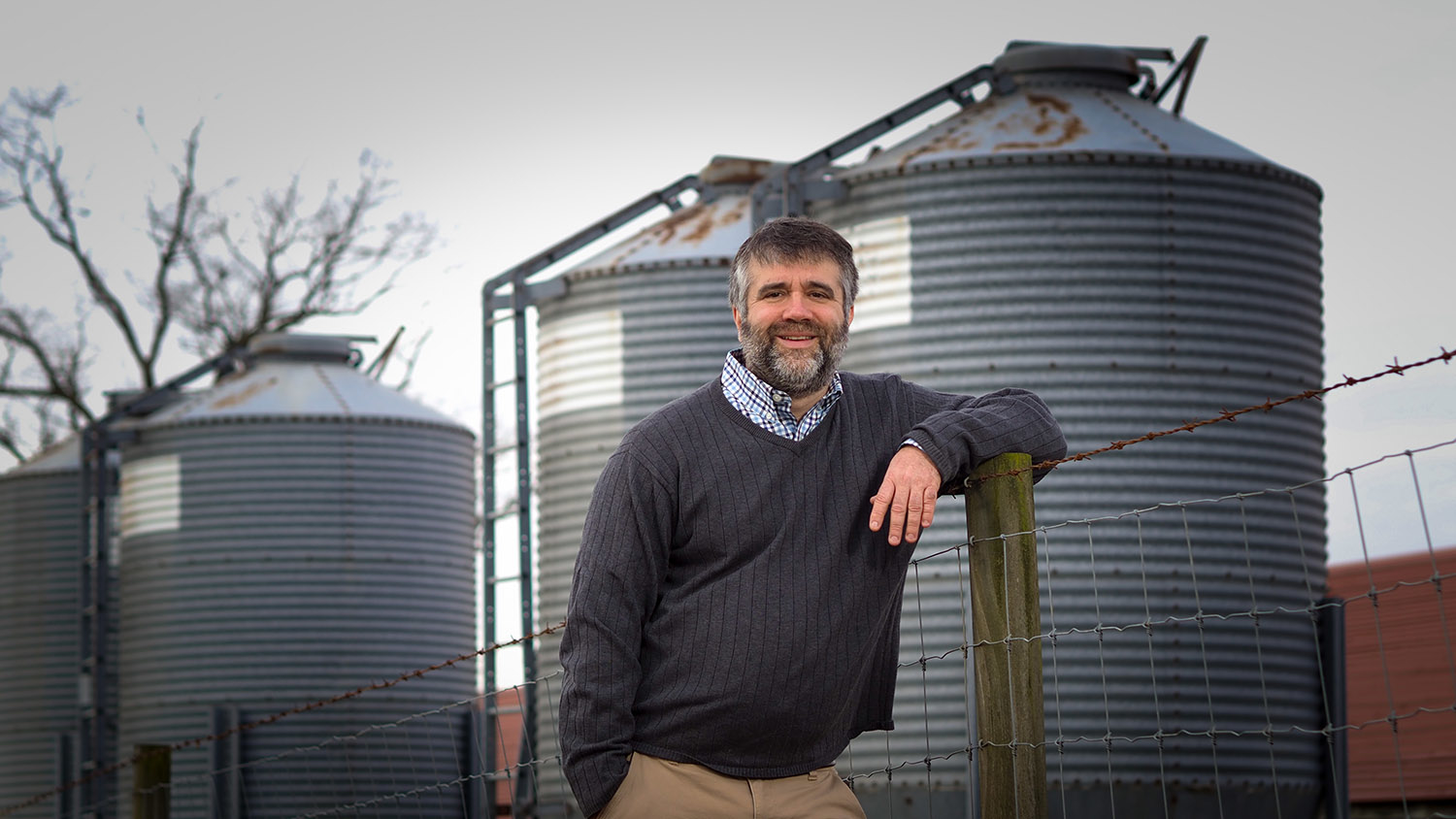 Man leaning against a fence post, with grain bins in the background.