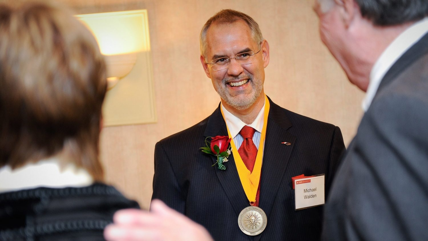 Man with medal around his neck speaking with two people