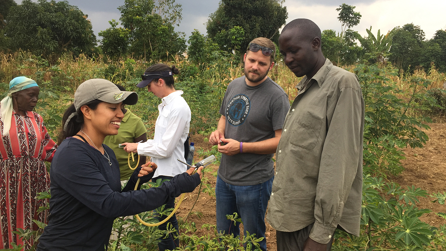 Gabriella Chavez (left) and William Sharpee (middle) talk with local cassava growers about how Cassava Mosaic Disease is transmitted.
