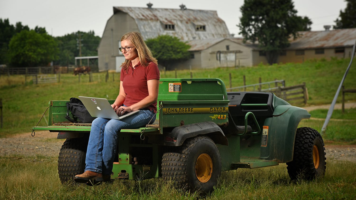 Animal Science student working on laptop sitting on a tractor.
