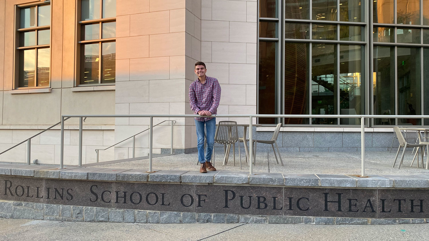 A young man standing on the steps of Emory University's School of Public Health