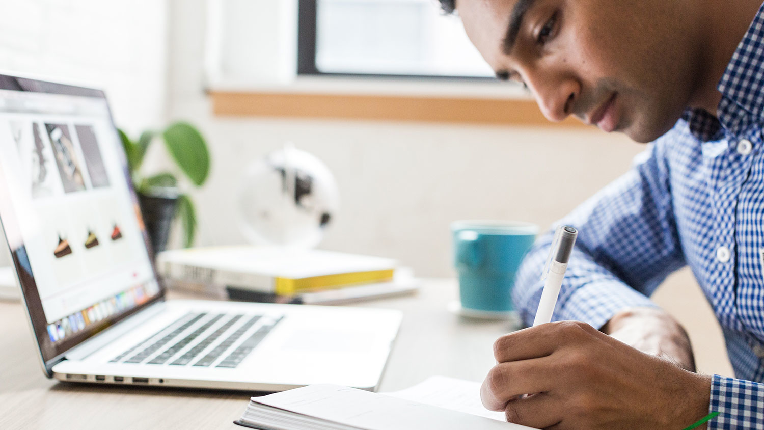 Young man taking notes and working on laptop