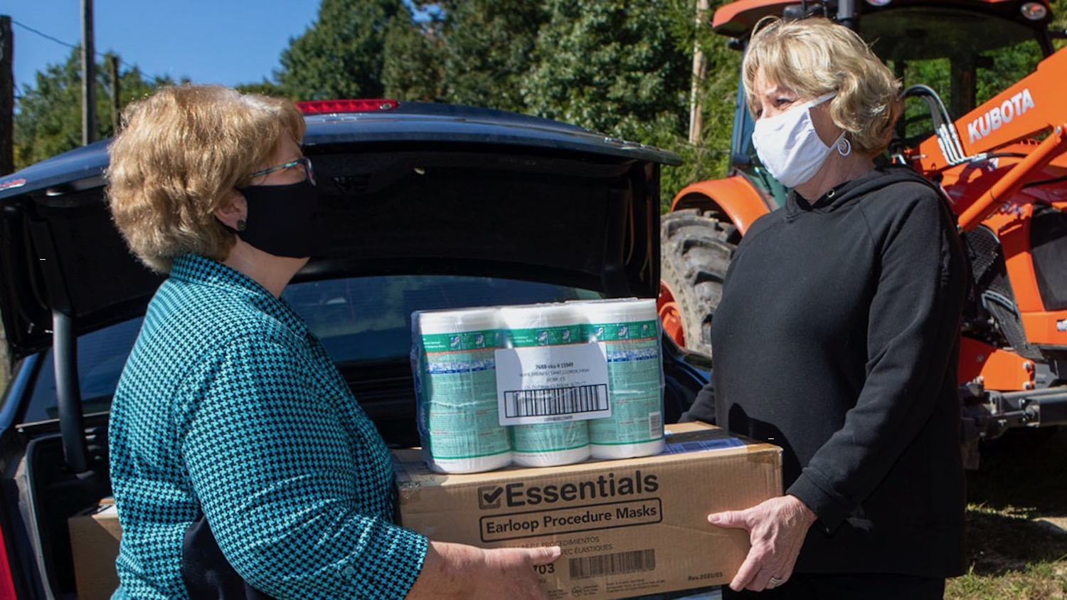 Dr. Robin Tutor Marcom, director of the North Carolina Agromedicine Institute handing protective masks and disinfectant wipes to Tracy Taylor, owner of Stone Mountain Farms in Vilas, N.C. Photos by Marie Freeman, Appalachian State University
