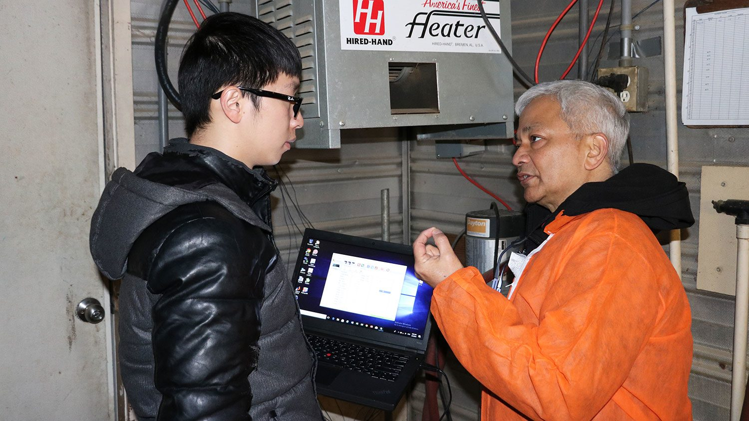 Sanjay Shah discusses temperature conditions in a swine nursery with graduate student Li Yu to evaluate the effectiveness of a solar powered heating system.
