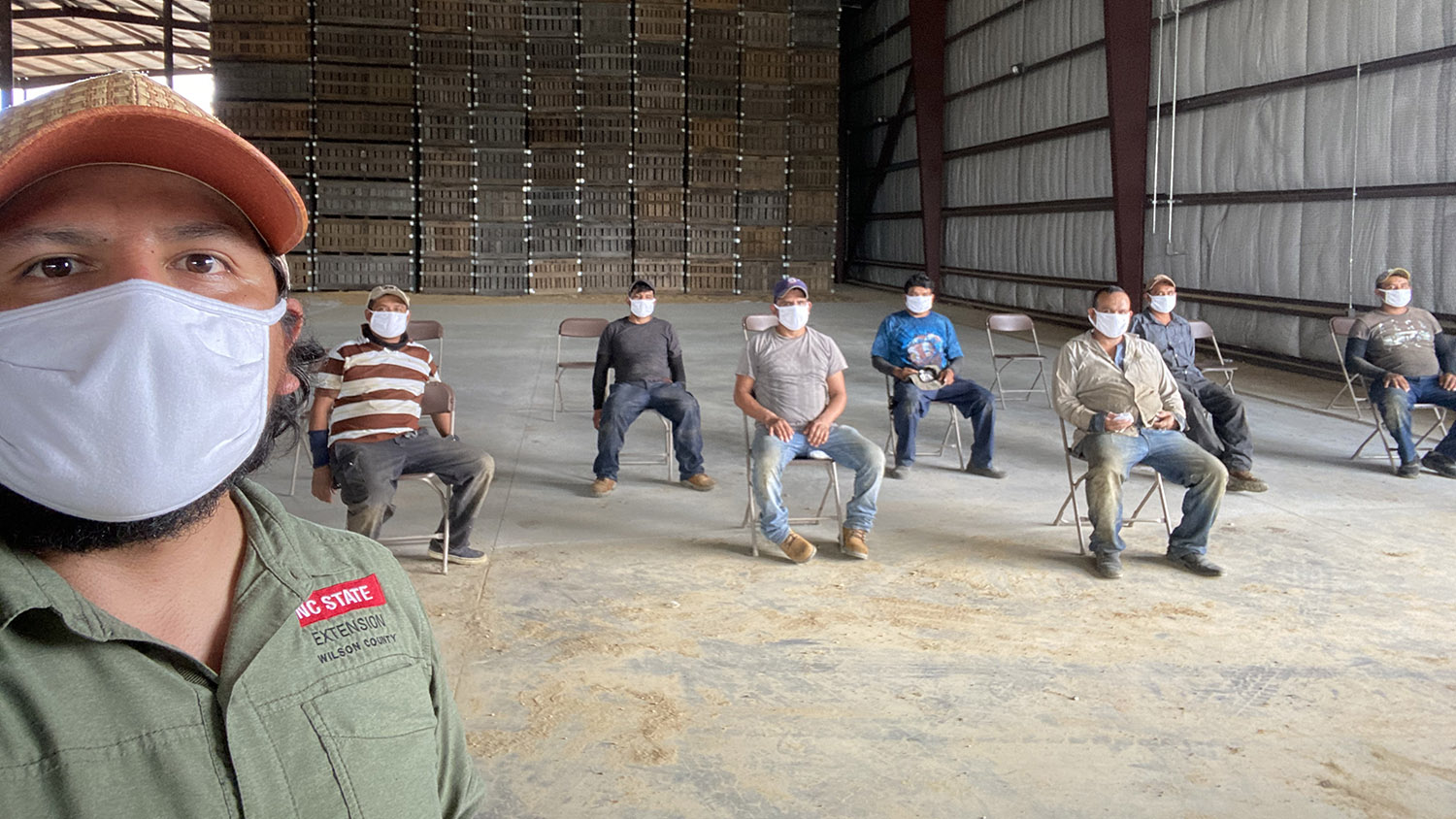 Socially distanced men with masks in a barn.
