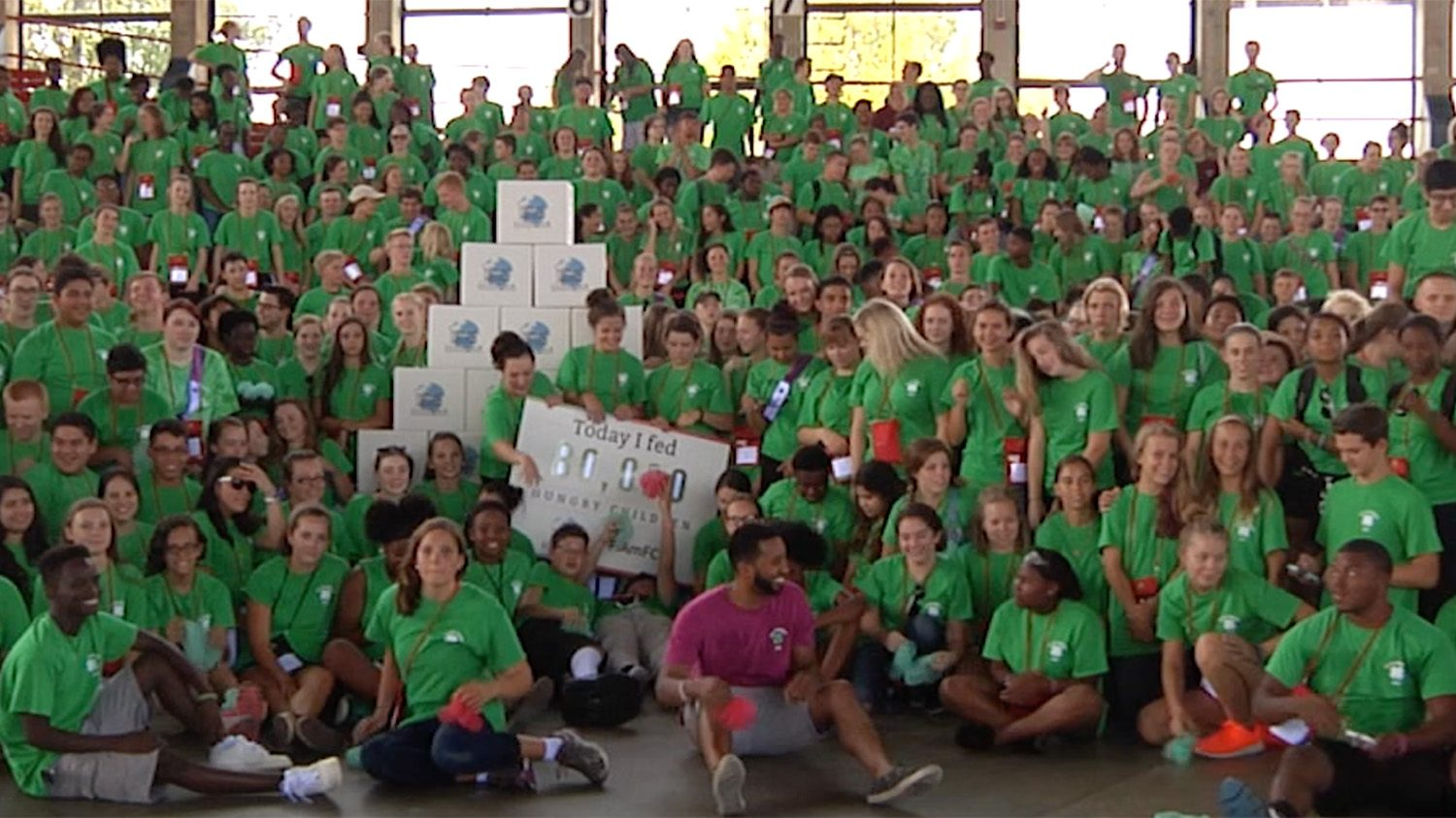 A large group of young people wearing green shirts and holding a large poster participating in the 2016 North Carolina State 4-H Congress