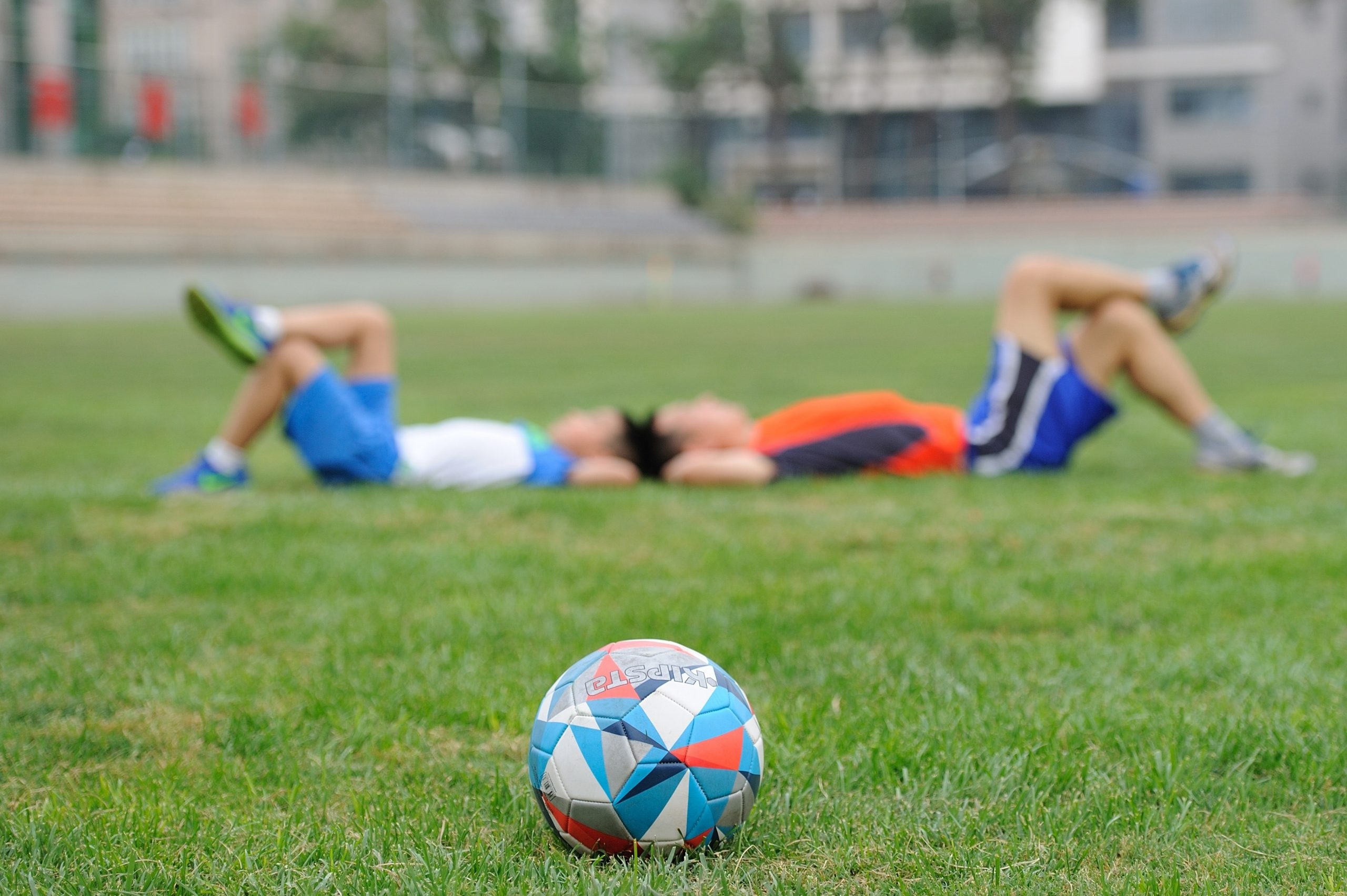 Students resting on turf after soccer game