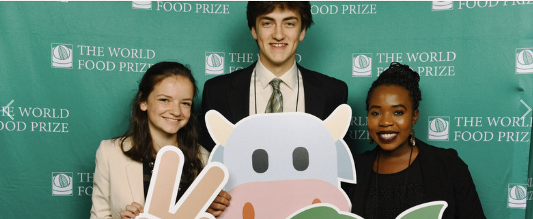 Three students standing in front of a World Food Prize banner