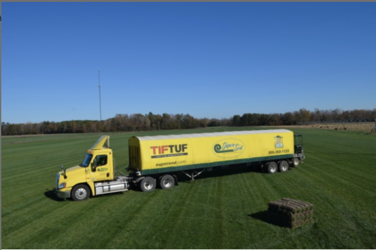 Yellow Super Sod tractor trailer on grass