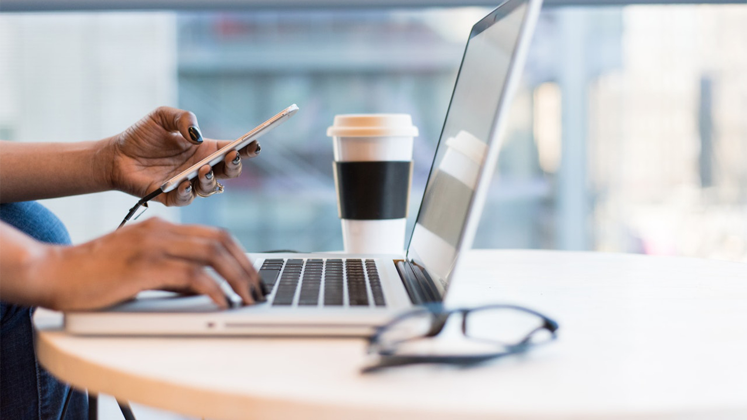 woman on laptop with a cup of coffee