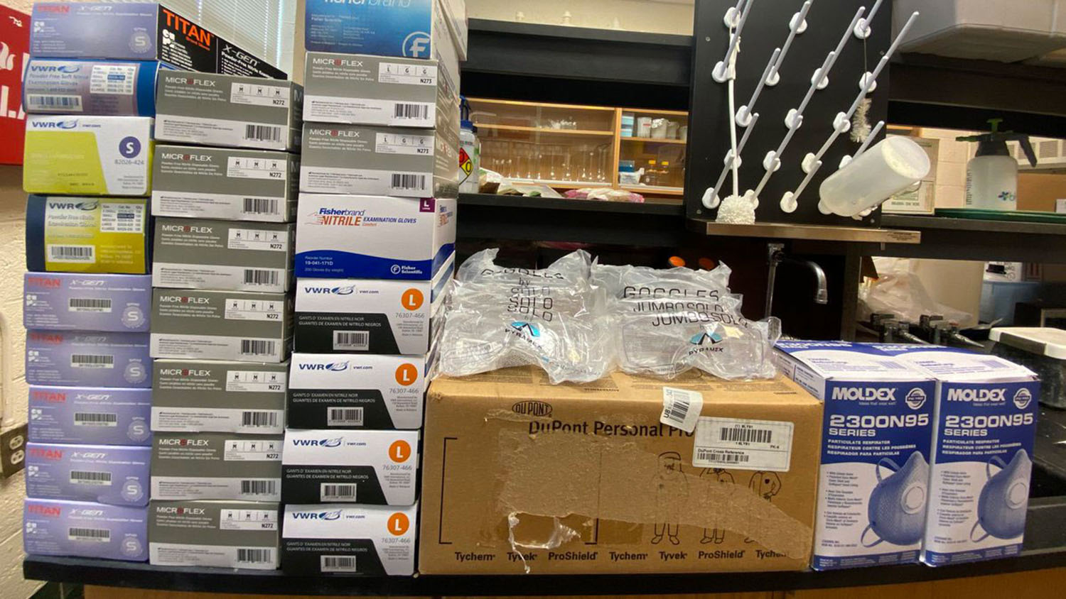 Boxes of gloves, safety goggles and masks in a lab.