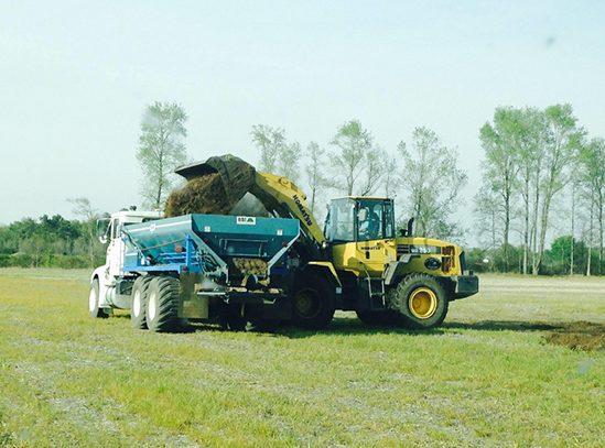A wheel loader dumps soil into a truck bed