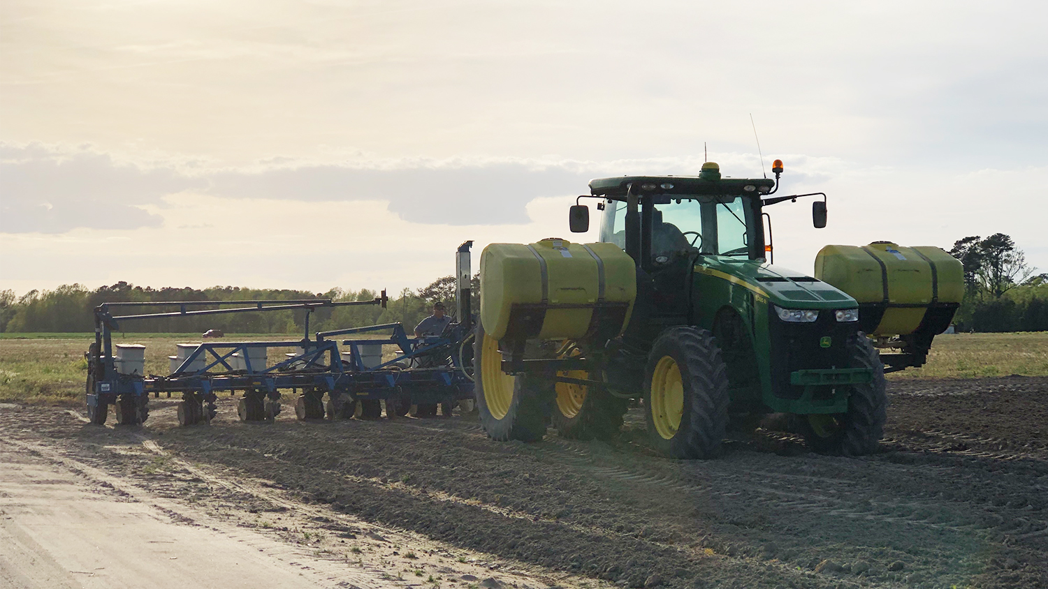 tractor pulls a planter across an empty field