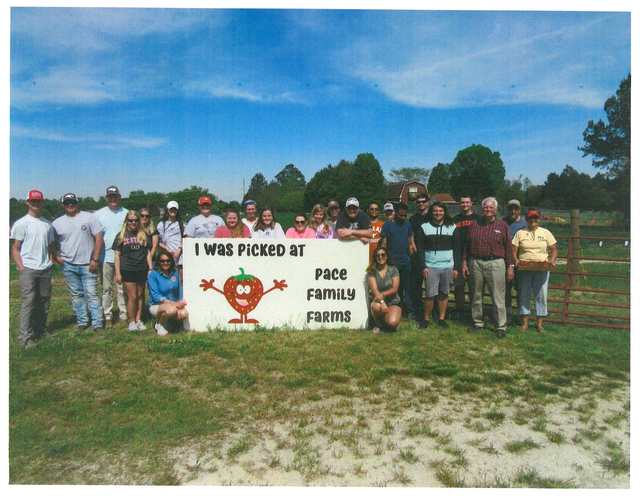 Group of students posed with a strawberry sign