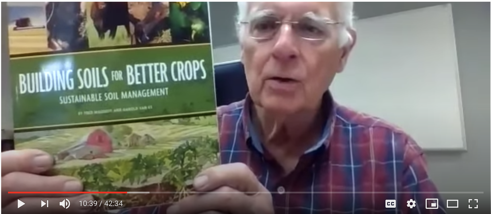 Man holding up book on cover crops