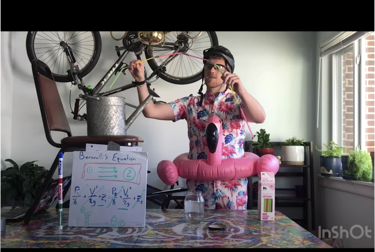 Man in bicycle helmet demonstrating a lab experiment