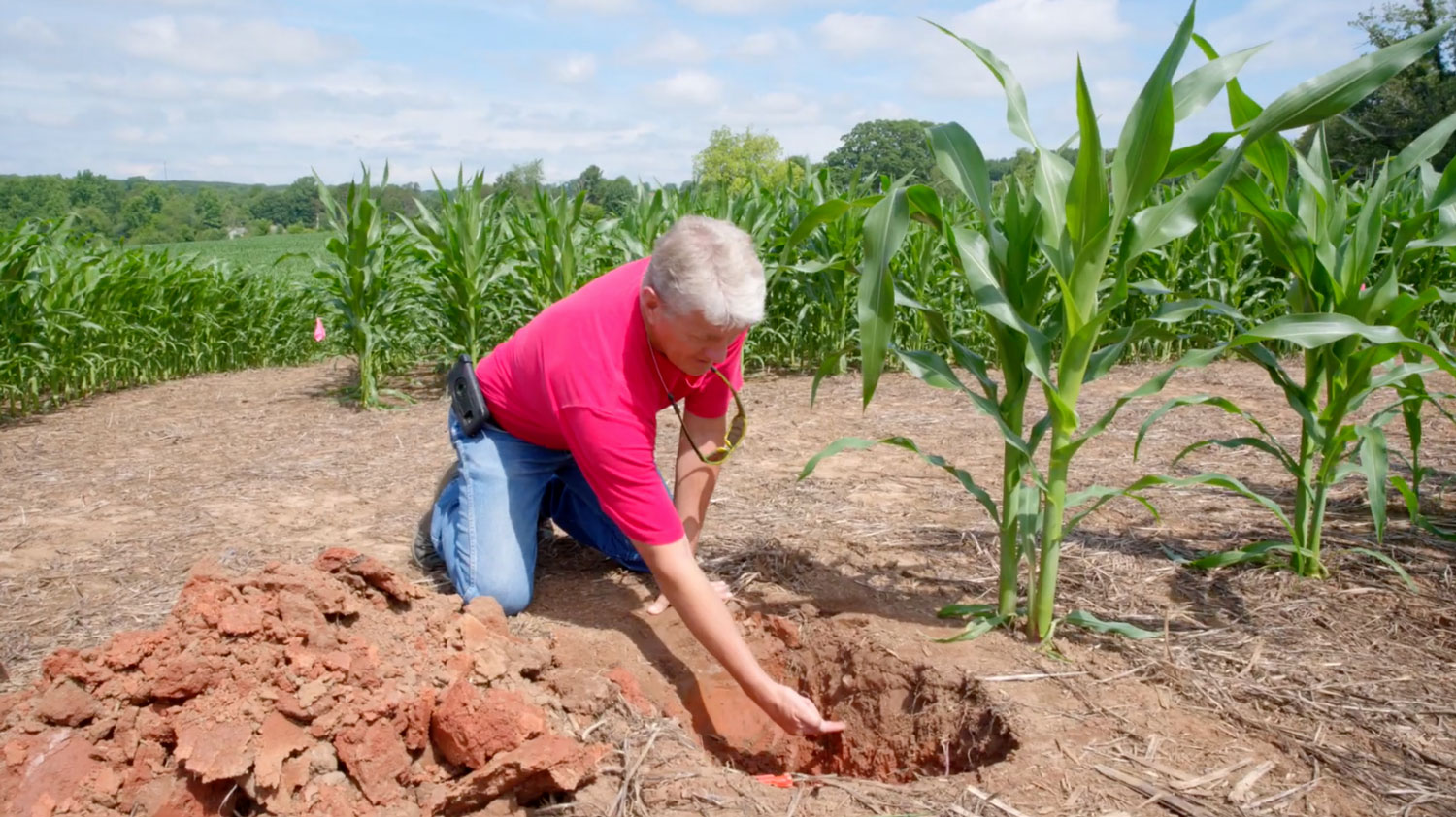 Man in a red shirt kneeling on the ground next to a hole