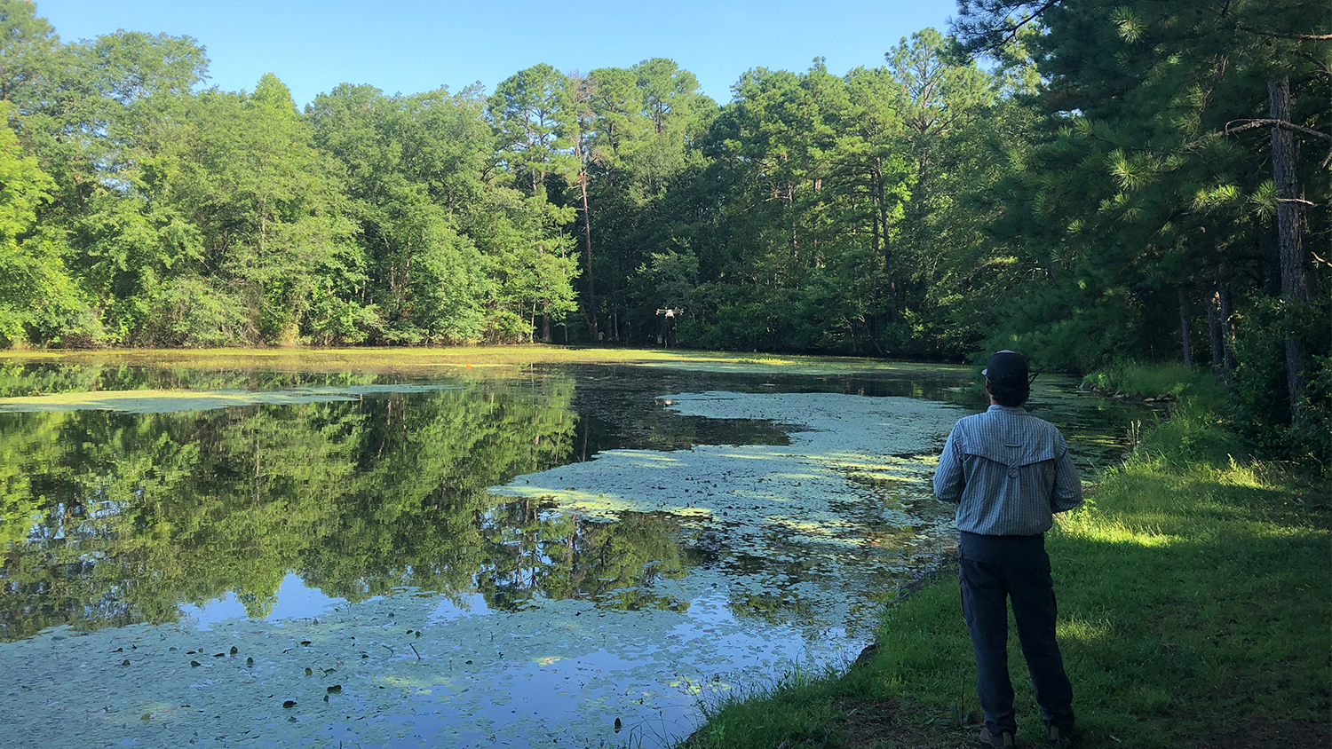 Man flying drone over pond