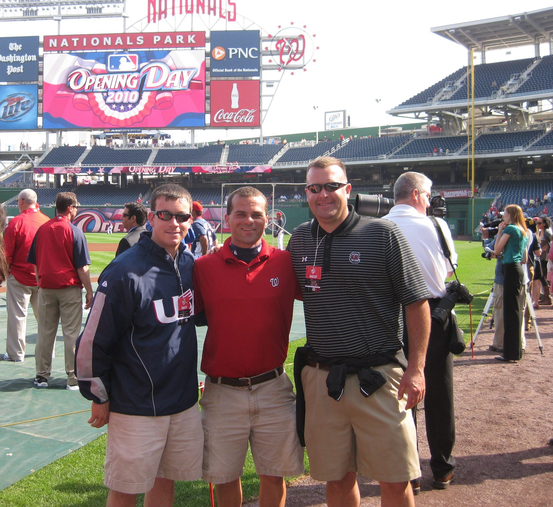 Three men pose on a baseball field