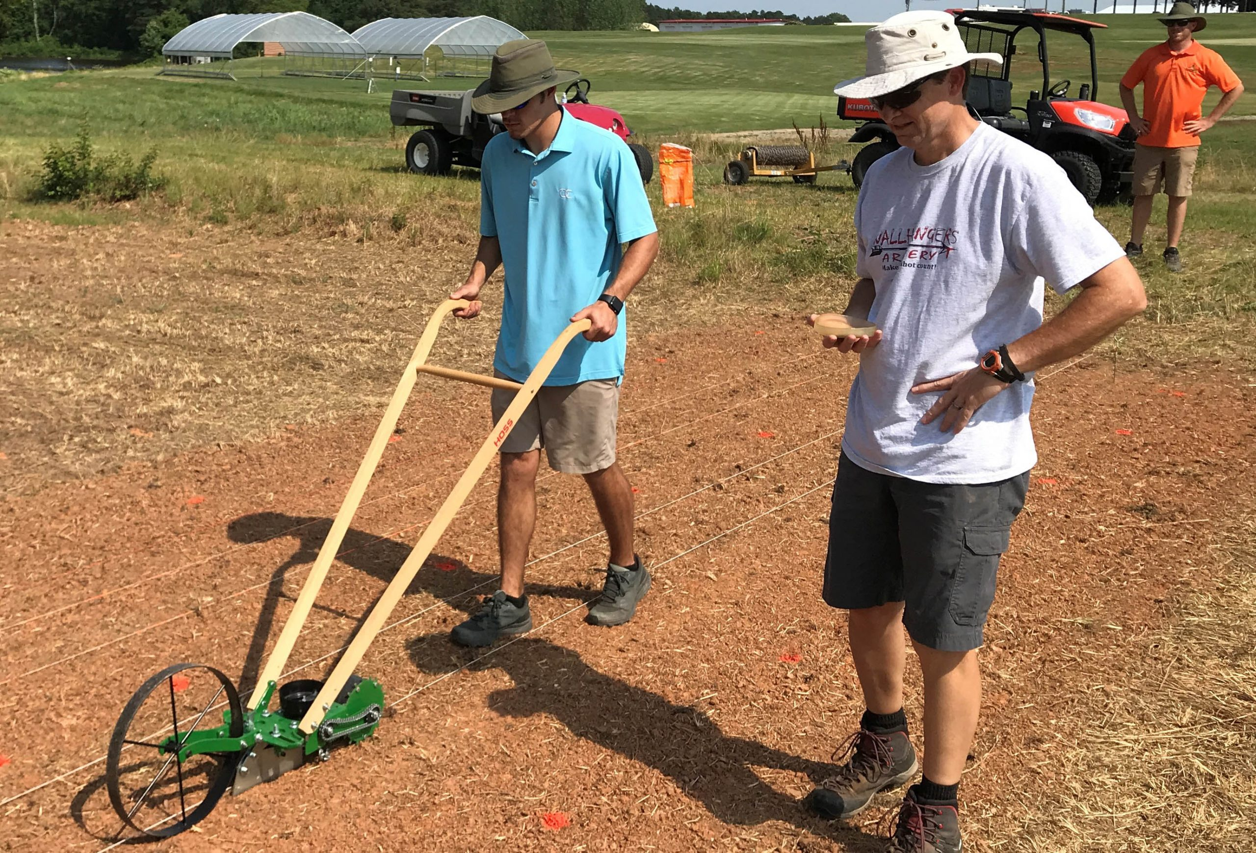 Two men spreading grass seed on bare soil