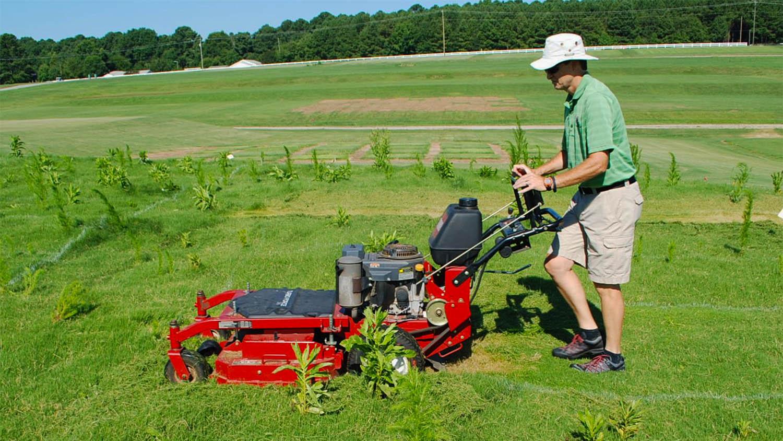 man in hat mowing grass