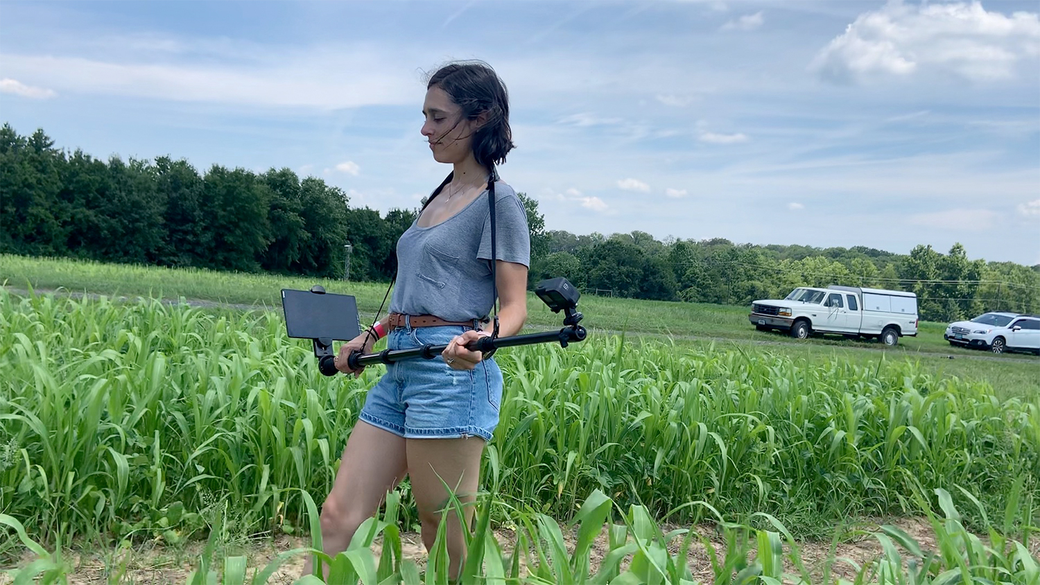 woman carrying a camera in a corn field