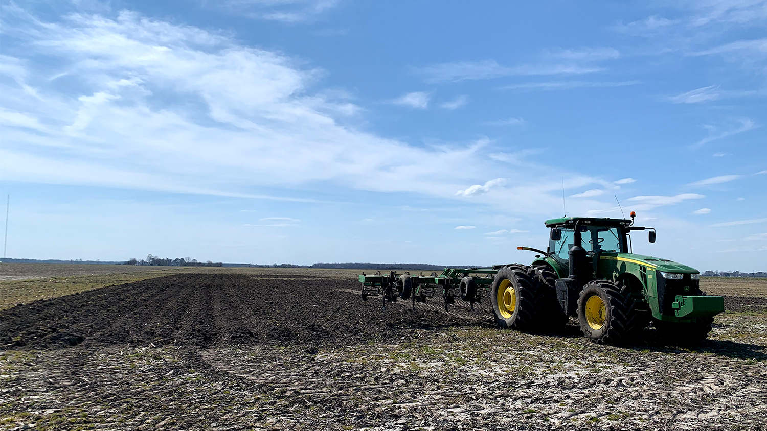 a green tractor pauses plowing an organic field