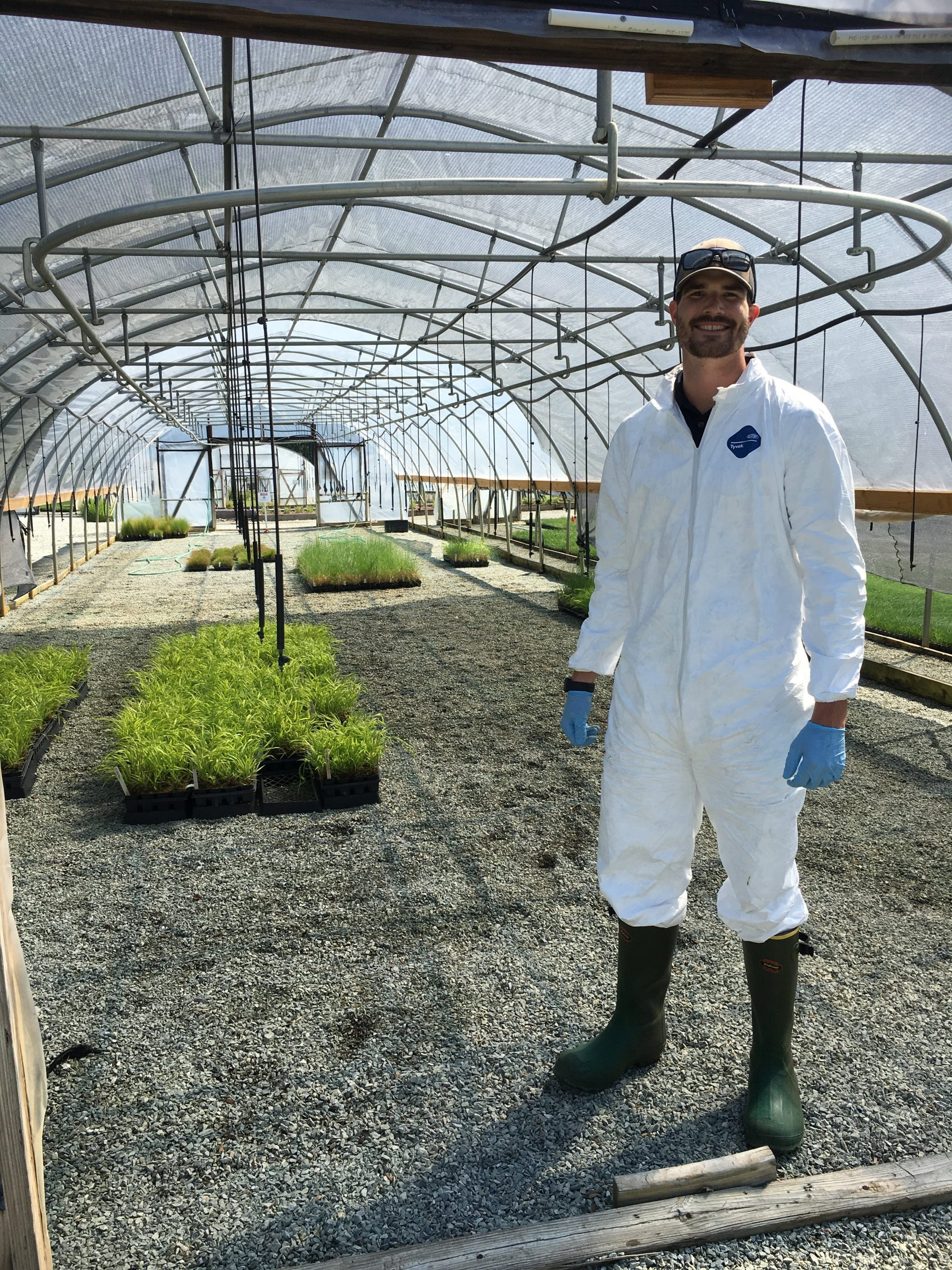 Man in lab coat standing in a turfgrass greenhouse