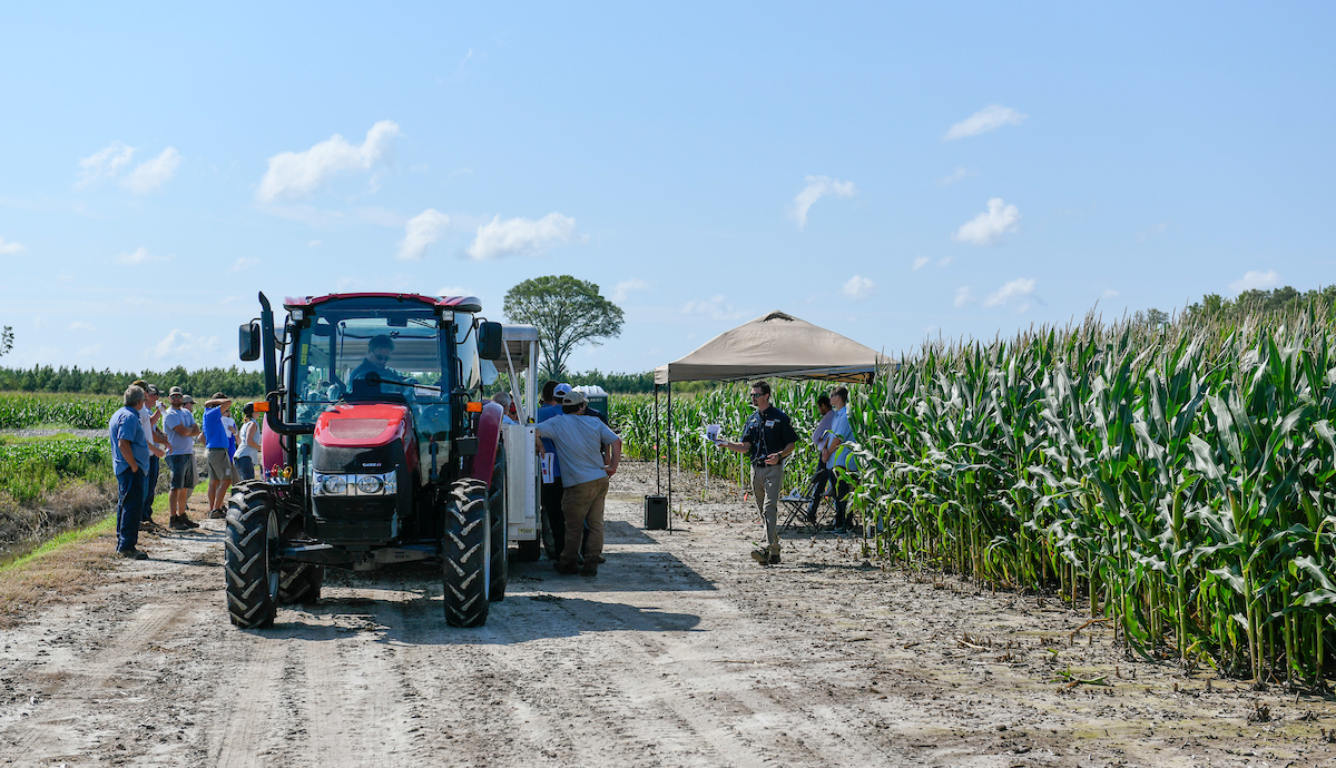 a tractor tours visitors to an Extension field day
