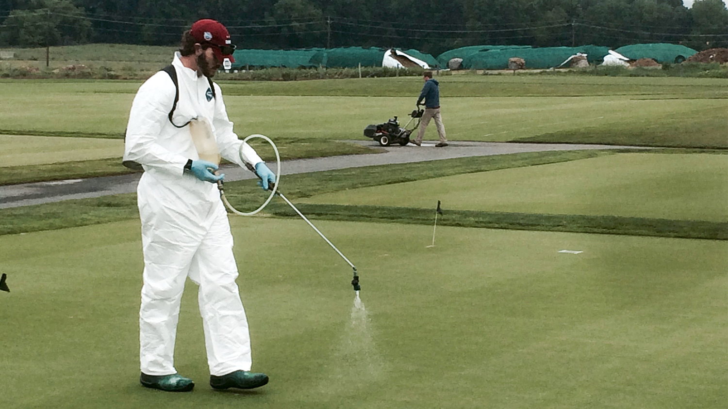 man in white protective suit sprays golf course green