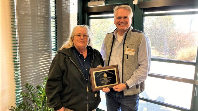 Cathy Herring stands next to Rick Seagroves as she receives the Distinguished Service Award from the Weed Science Society of North Carolina.