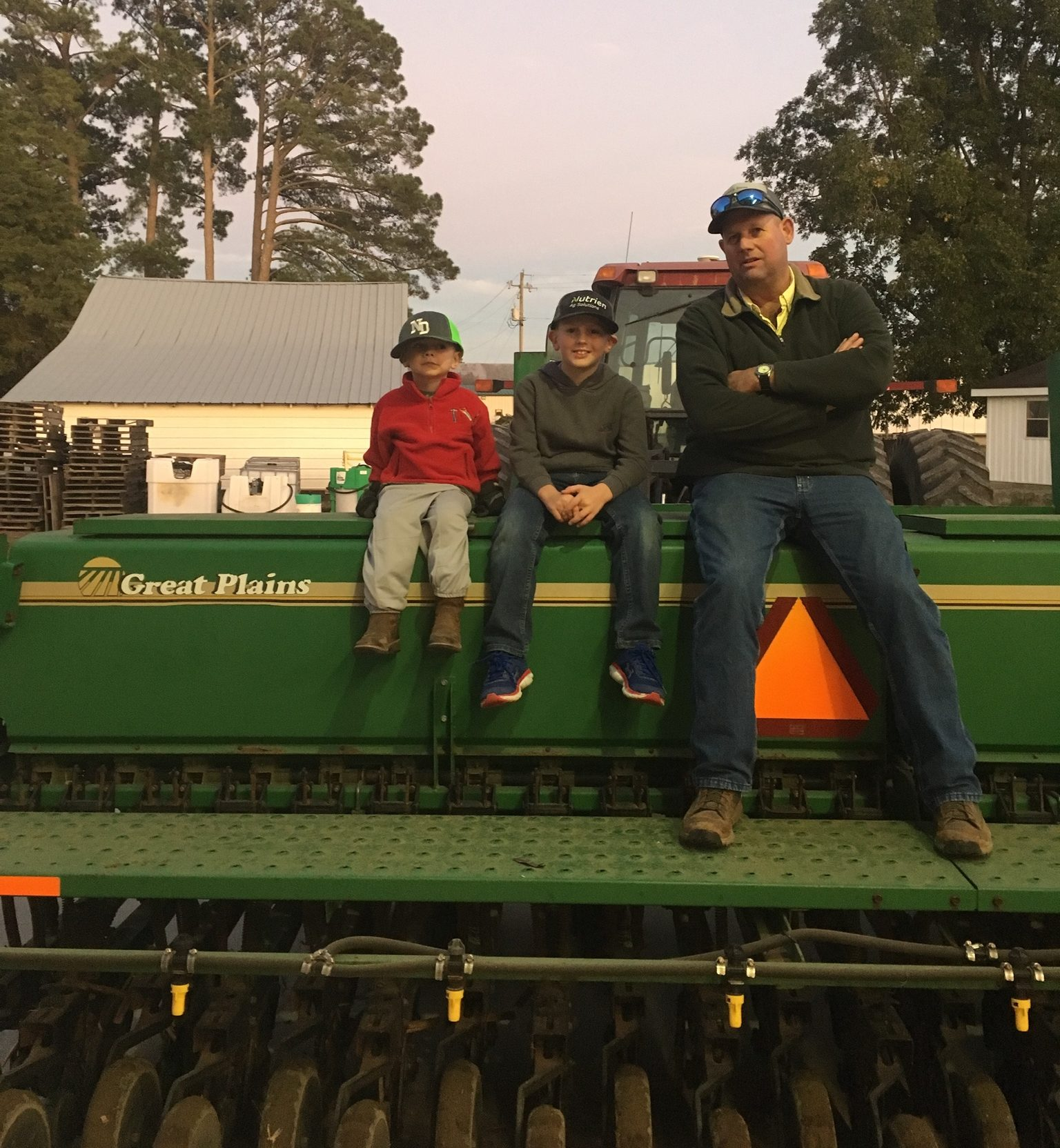 Grandfather and sons sit on a planter