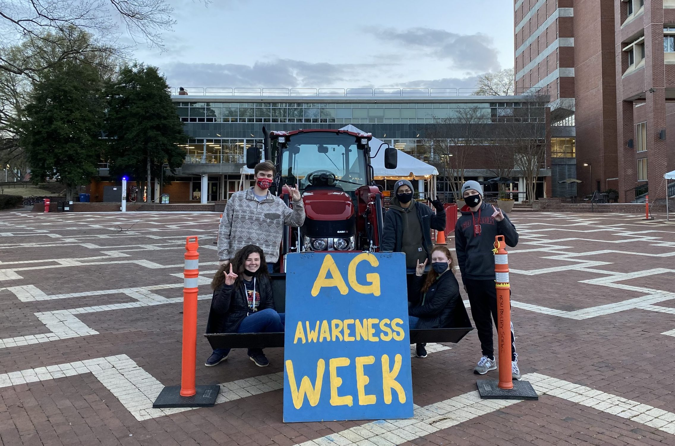 a group of students pose with a tractor on the NC State Brickyard