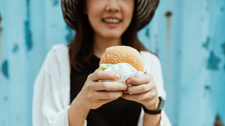 woman holding a sesame seed bun burger