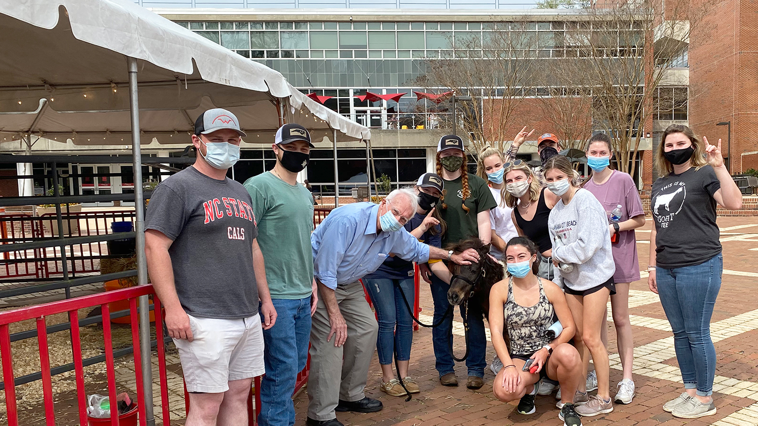 group poses with miniature horse on NC sTate Brickyard