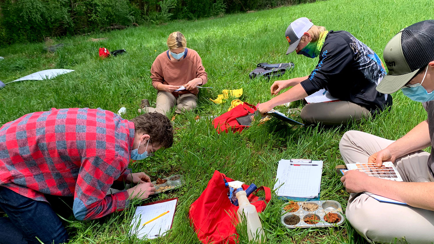 students study soil samples on grass
