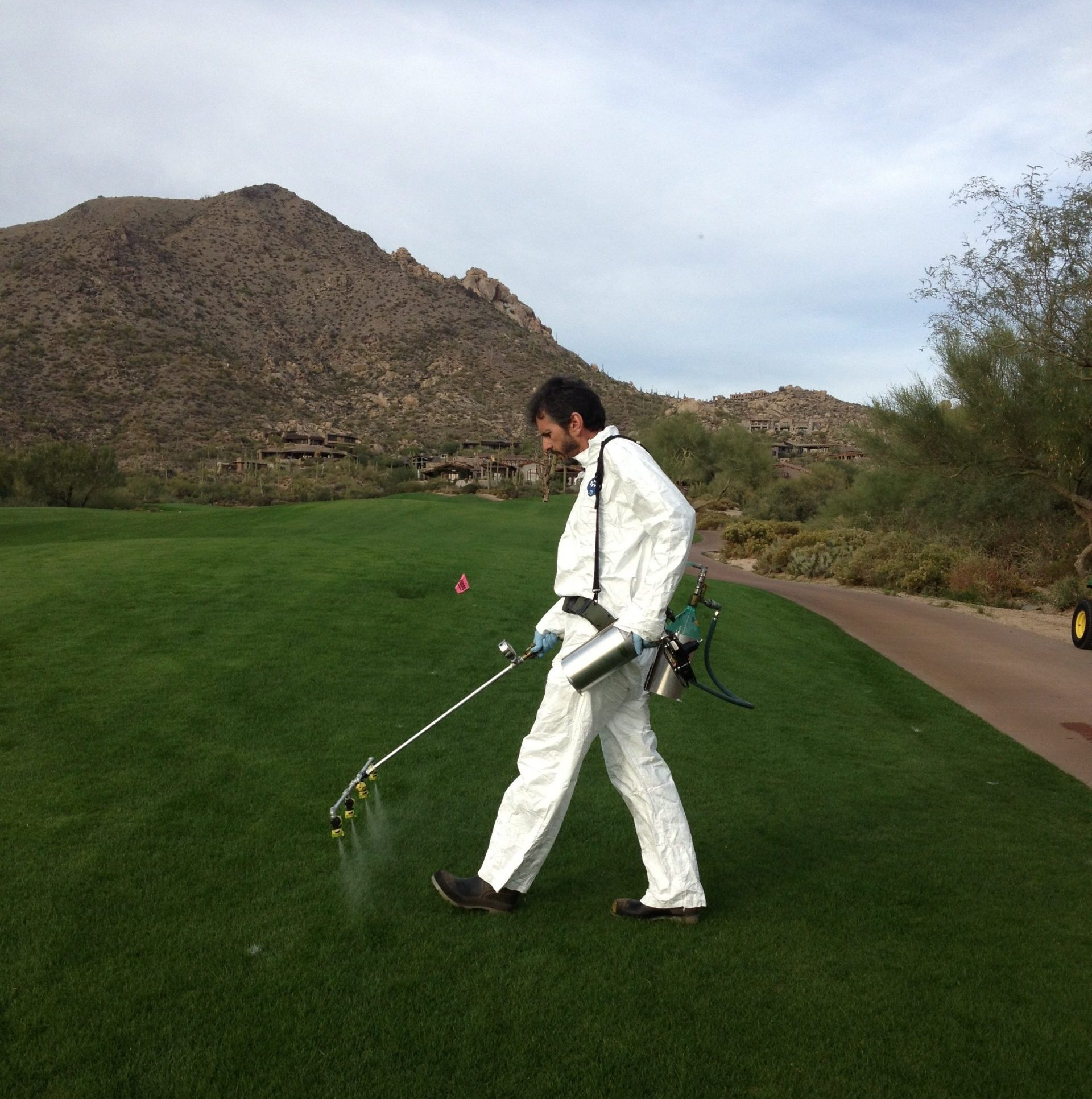 Man in white coveralls spraying turfgrass