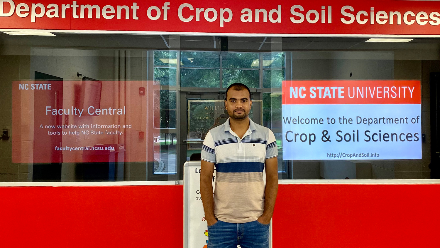 Man in front of NC State display