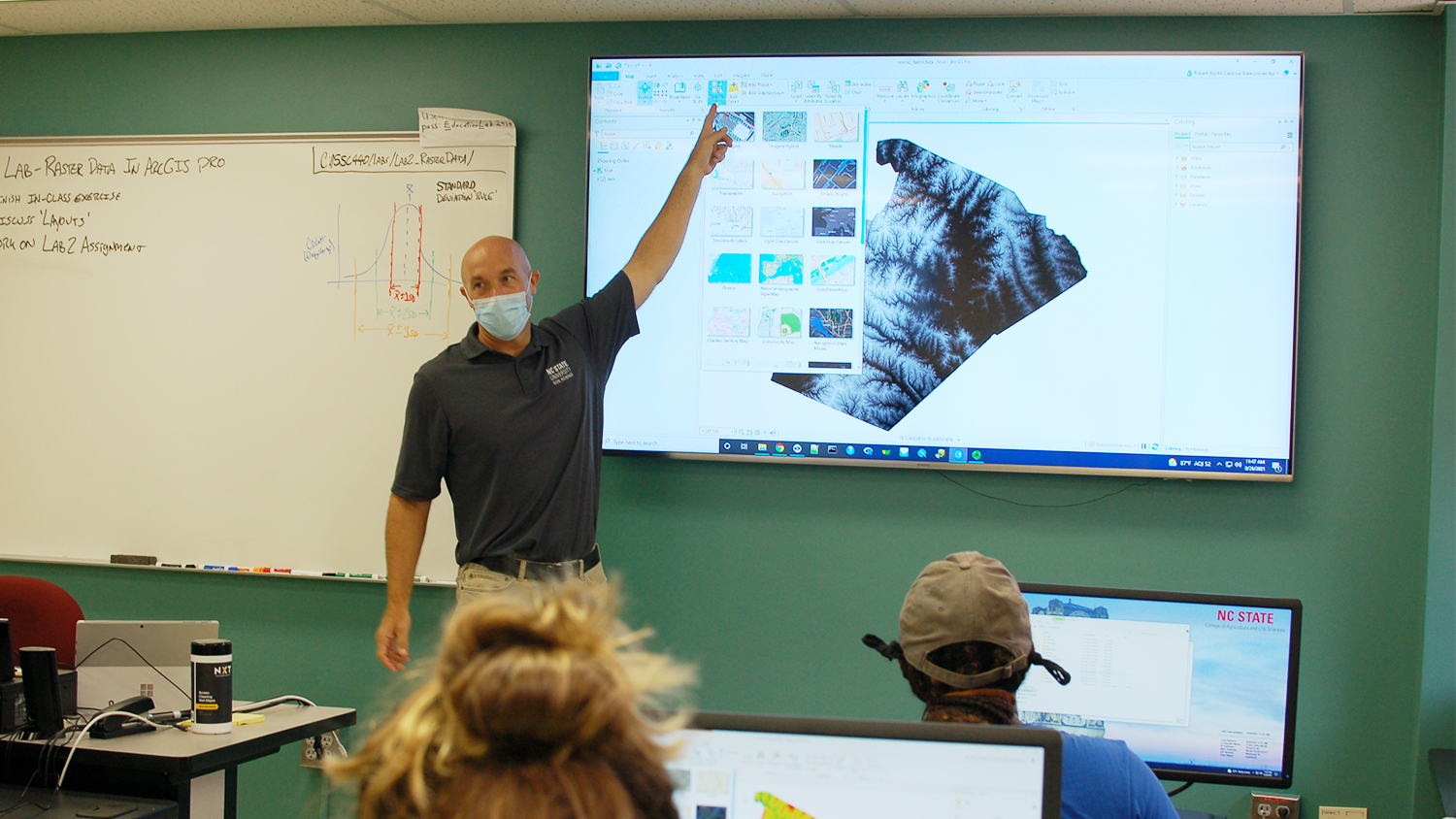 A man teaches graphical mapping at a white board