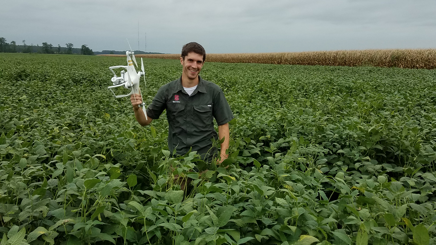 Researcher holds drone in NC farm field