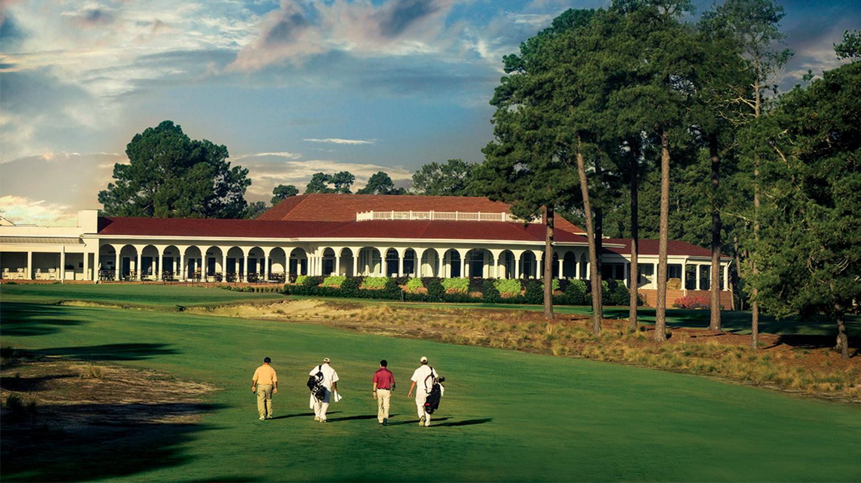 Golfers walk Pinehurst Number 2's 18th fairway